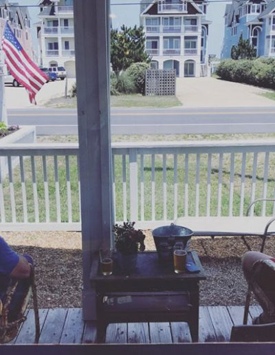Two people on the porch enjoying a beer at Jack Brown's Kill Devil Hills, NC.